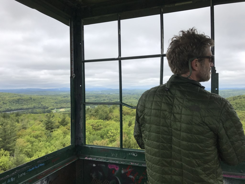 Joel Clement in the fire tower on Mount Pisgah in Winthrop. Clement, who began his career as a forest biologist, became an expert on building resilience to climate change in the Arctic, helping three Alaskan villages in peril from rising seas.
