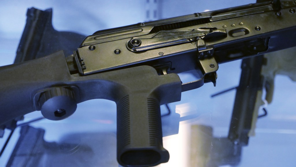 A device called a bump stock is attached to a semi-automatic rifle. The Trump administration is proposing banning bump stocks, which allow guns to mimic fully automatic fire and were used in last year's Las Vegas massacre. The Justice Department's regulation, announced Saturday would classify the device as a machine gun prohibited under federal law.