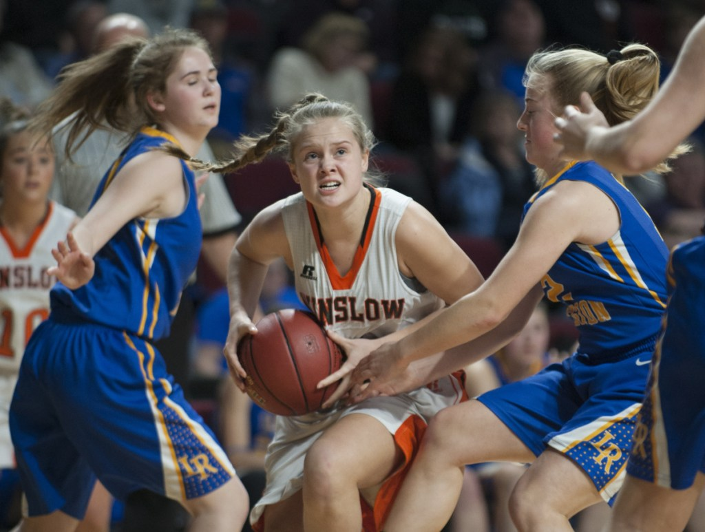 Winslow's Silver Clukey splits Lake Region defenders Rachel Shanks, left and Shauna Hancock on her way to the basket during the Class B state championship game Friday night at the Cross Insurance Center in Bangor.