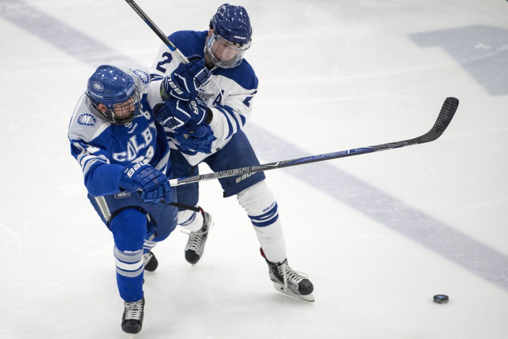Colby College's Phil Klitirinos, left, collides with University of New England defenseman Ian Rodden during the first period Saturday night at the Harold Alfond Forum in Biddeford.
