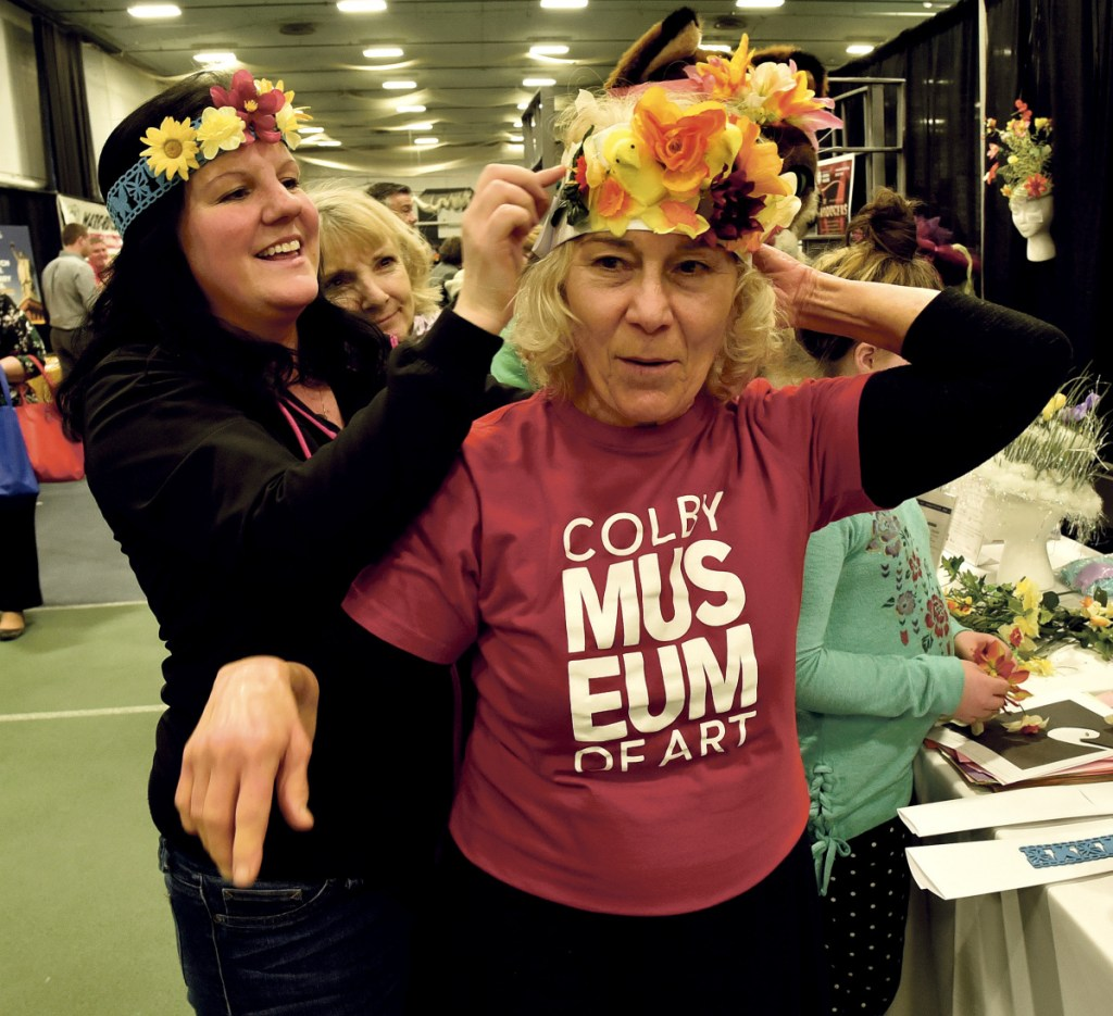 Tonya Clark, left, of T-Mobile, fastens a spring bonnet on Natty Lazavian, of the Colby College Museum of Art, on Thursday during the Business to Business event at Colby College in Waterville. The colorful bonnets were courtesy of the Waterville Creates! art program.