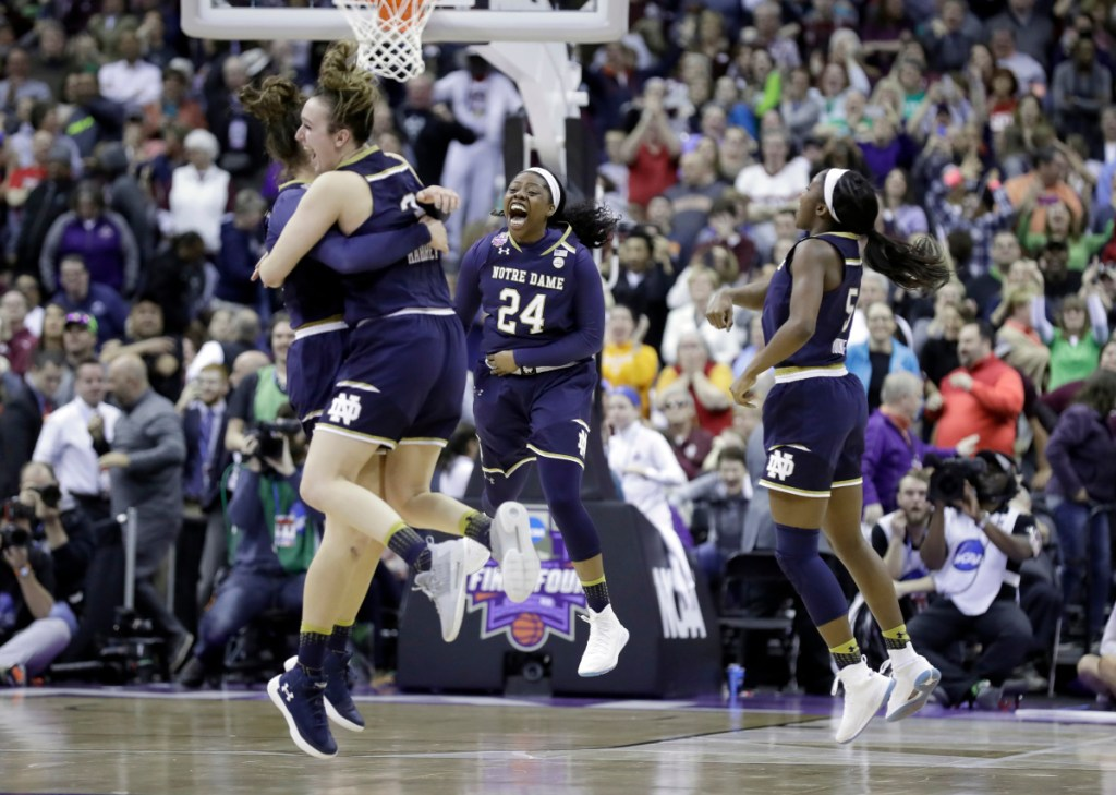 Notre Dame's Arike Ogunbowale (24) celebrates with teammates after making a 3-point basket to defeat Mississippi State 61-58 in the final of the women's NCAA Final Four college basketball tournament, Sunday, April 1, 2018, in Columbus, Ohio. (AP Photo/Ron Schwane)