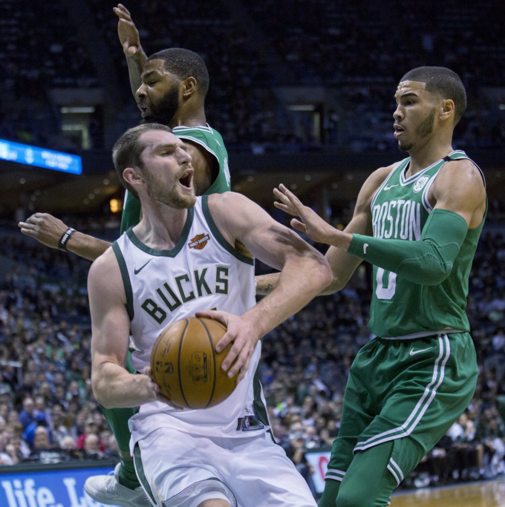 Milwaukee center Tyler Zeller, center, is defended by Boston forward Marcus Morris, left, and Jayson Tatum, right, during Tuesday's game in Milwaukee.