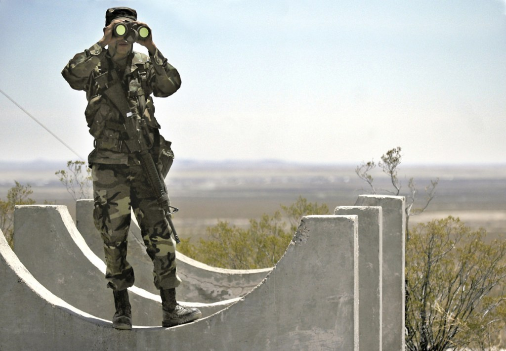 Army National Guard Spc. Gustavo Gutierrez, 23, of Las Cruces, N.M., scans the U.S./Mexico border from the top of Radar Hill, near Columbus, N.M., in June 2006.