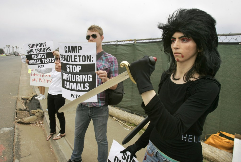 Nasim Aghdam, right, joins members of People for the Ethical for Animals protesting at the main gate of Marine Corps' Camp Pendleton in Oceanside, Calif., in August 2009. Law enforcement officials have identified her as the person who opened fire with a handgun Tuesday at YouTube headquarters in San Bruno, Calif., wounding three people before fatally shooting herself.