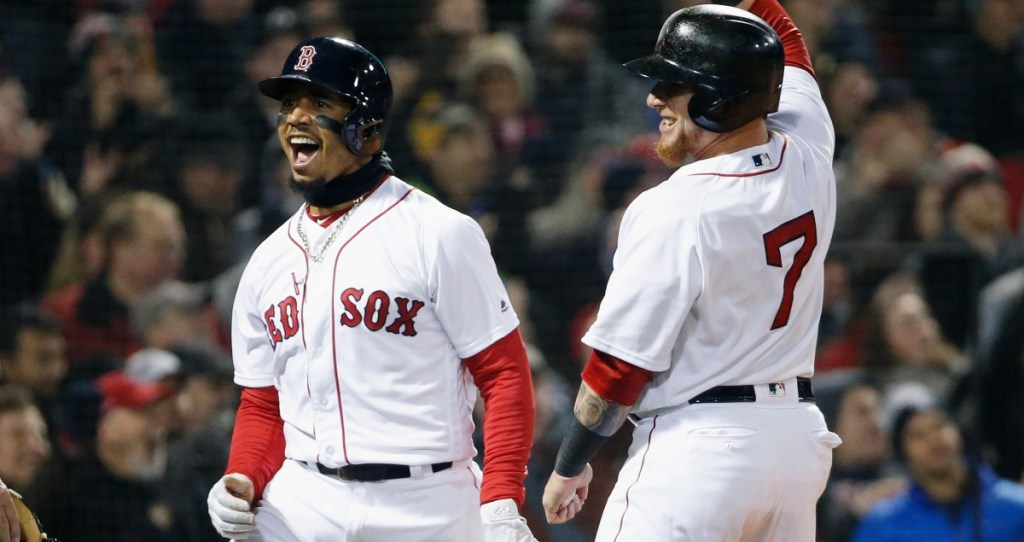Boston Red Sox's Mookie Betts, left, celebrates with Christian Vazquez (7) after scoring on a triple by Andrew Benintendi during the second inning of a baseball game against the New York Yankees in Boston, Tuesday, April 10, 2018. ()
