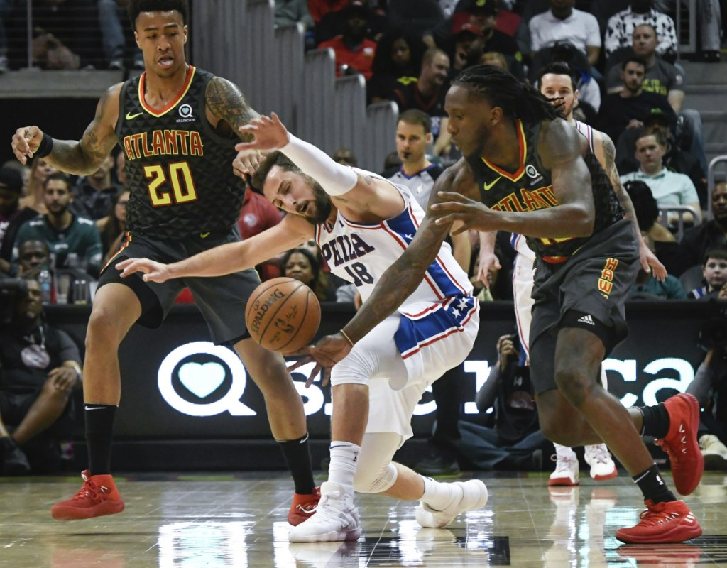 Philadelphia's Marco Belinelli has the ball stolen by Atlanta's Taurean Prince, right, as John Collins looks on during the second half Tuesday night in Atlanta.