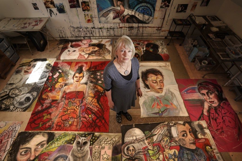 """Martha Miller poses for a photo with paintings from her current project, the """"Lisbeth Series,"""" in her studio in Woolwich. Over the past several weeks, Miller has been creating highly graphic, sometimes disturbing and sometimes beautiful images of her daughter, who is disabled."""