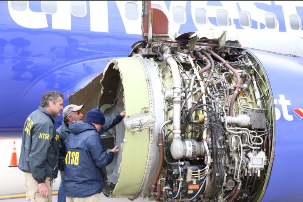 National Transportation Safety Board investigators examine damage to the engine of the Southwest Airlines plane that made an emergency landing in Philadelphia on Tuesday.