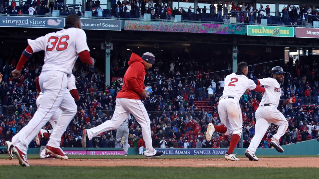 Boston Red Sox designated hitter Hanley Ramirez, right, is chased by teammates as he celebrates after his bases-loaded walkoff single in the twelfth inning Thursday against the Tampa Bay Rays at Fenway Park in Boston.