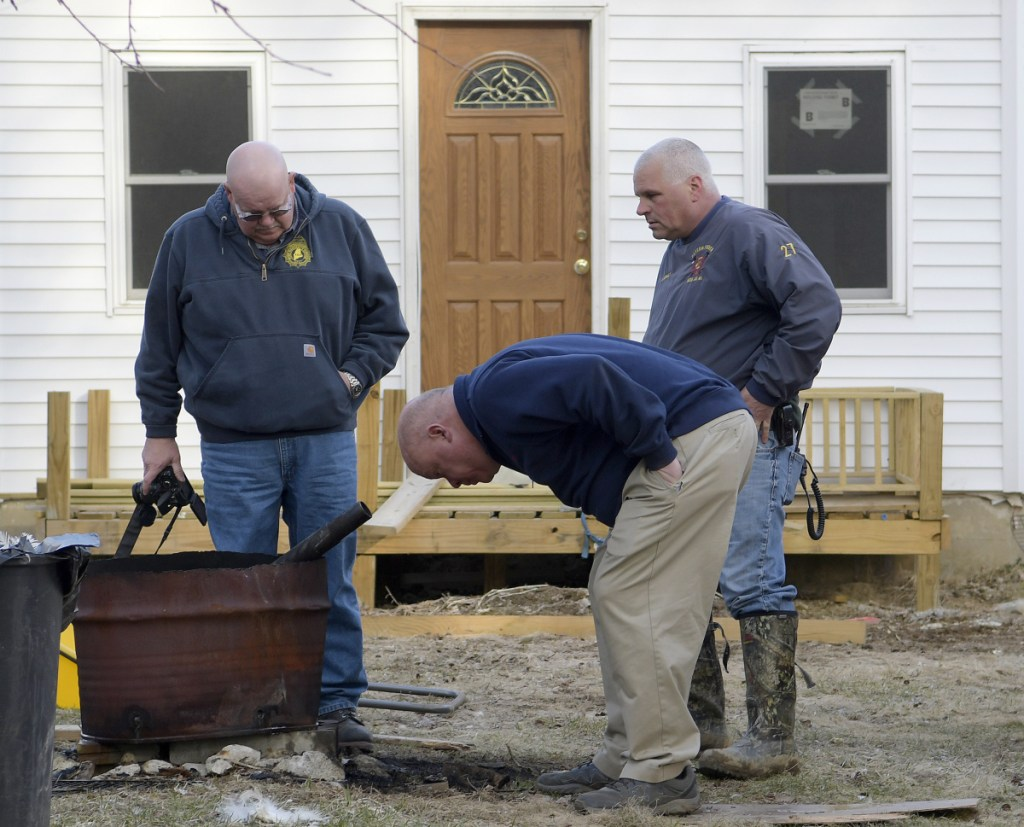 Office of State Fire Marshal investigator Ken MacMaster, left, Winthrop Fire Chief Dan Brooks and Winthrop firefighter Mark Arsenault inspect a burn barrel Tuesday outside a residence in Winthrop, where Leon Deblois suffered leg burns.