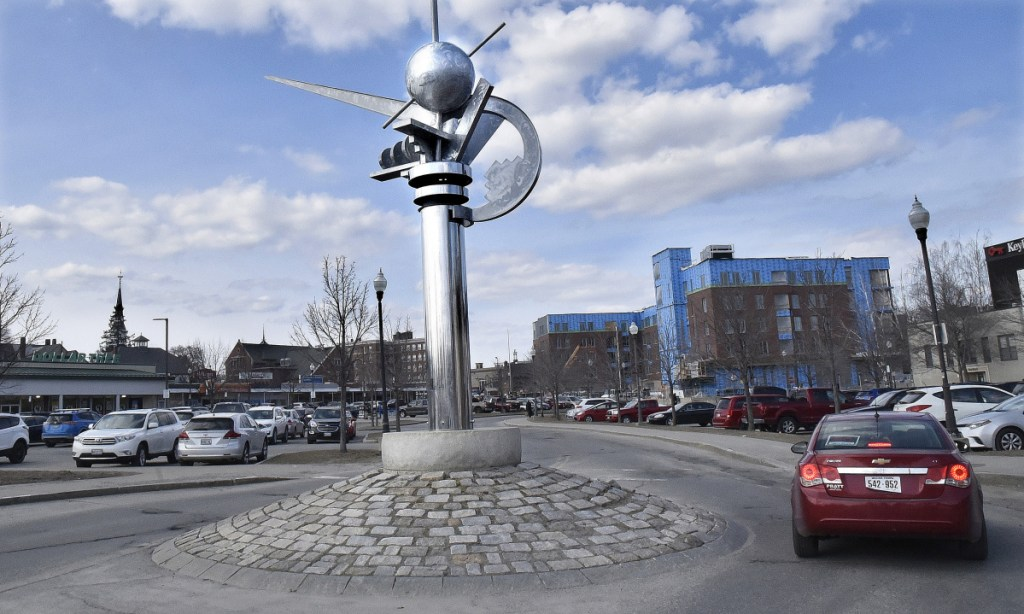 """A vehicle negotiates the turn around """"The Ticonic"""" sculpture recently in the middle of the Concourse in Waterville. The City Council has approved taking funds from a public works account to pay for moving the sculpture to its planned site on the RiveWalk."""