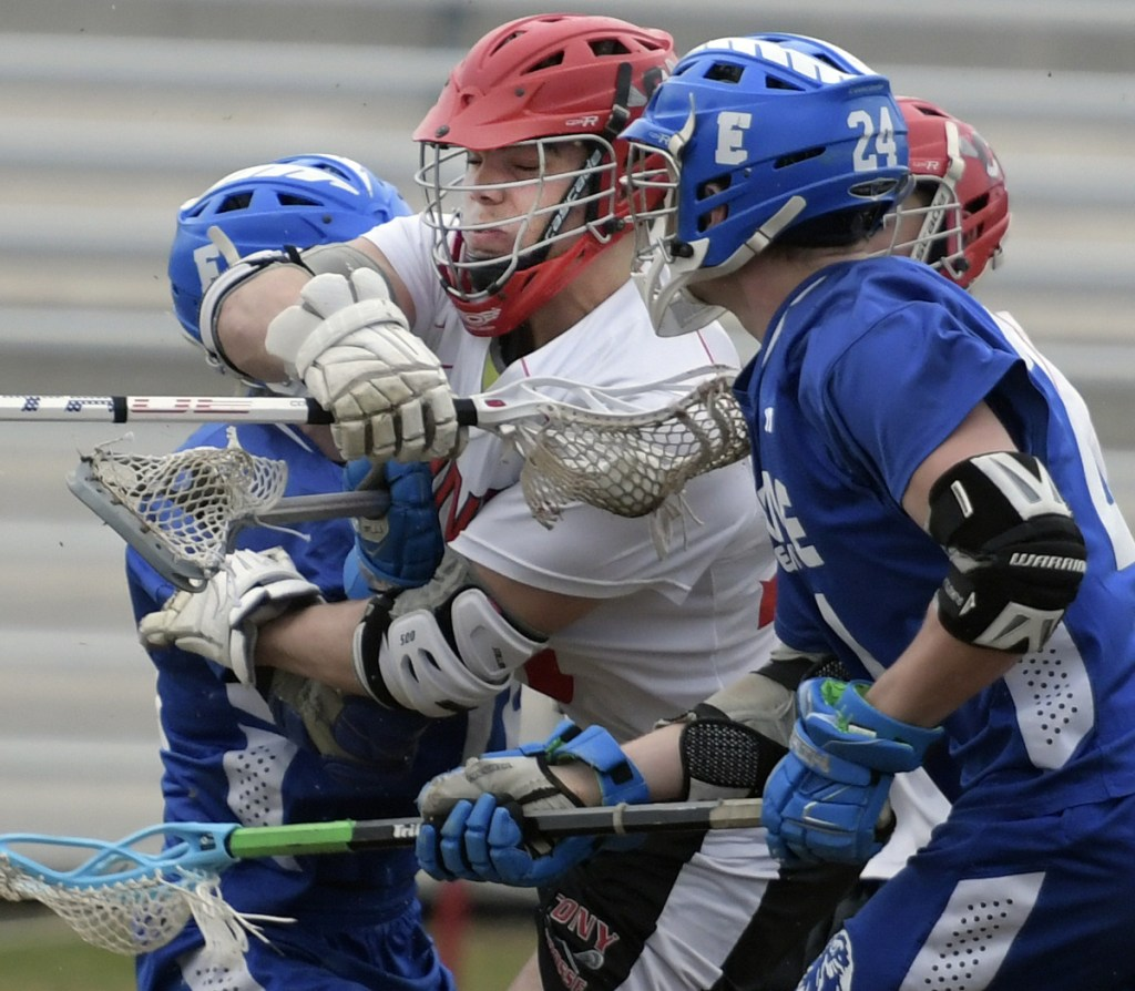 Cony's Nic Mills, center, crashes through Erskine defenders during a lacrosse match Wednesday in Augusta.
