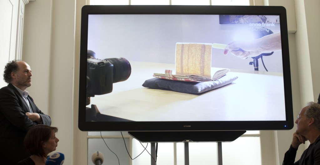 A video shows how two pages taped off with brown masking paper from Anne Frank's diary were photographed to reveal her writing, during a news conference at The Anne Frank Foundation's office in Amsterdam, Netherlands, on Tuesday. Standing at left is the foundation's director, Ronald Leopold.