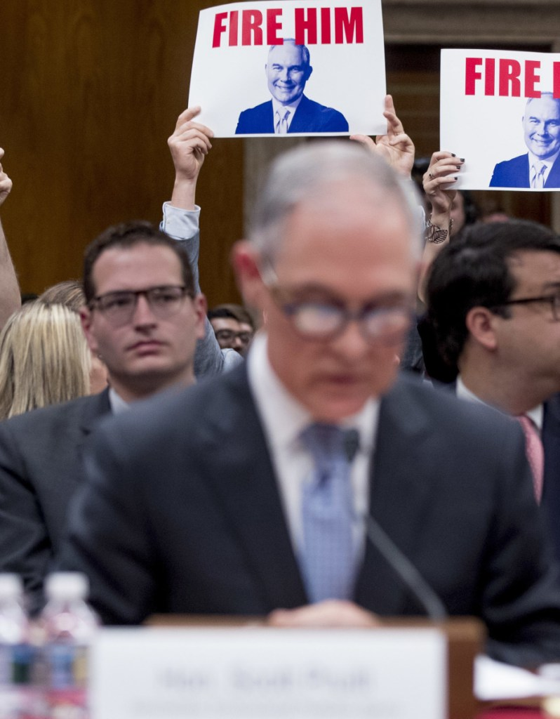 """Members of the audience hold signs reading """"Fire Him"""" as EPA Administrator Scott Pruitt, center, testifies Wednesday before a Senate appropriations subcommittee."""