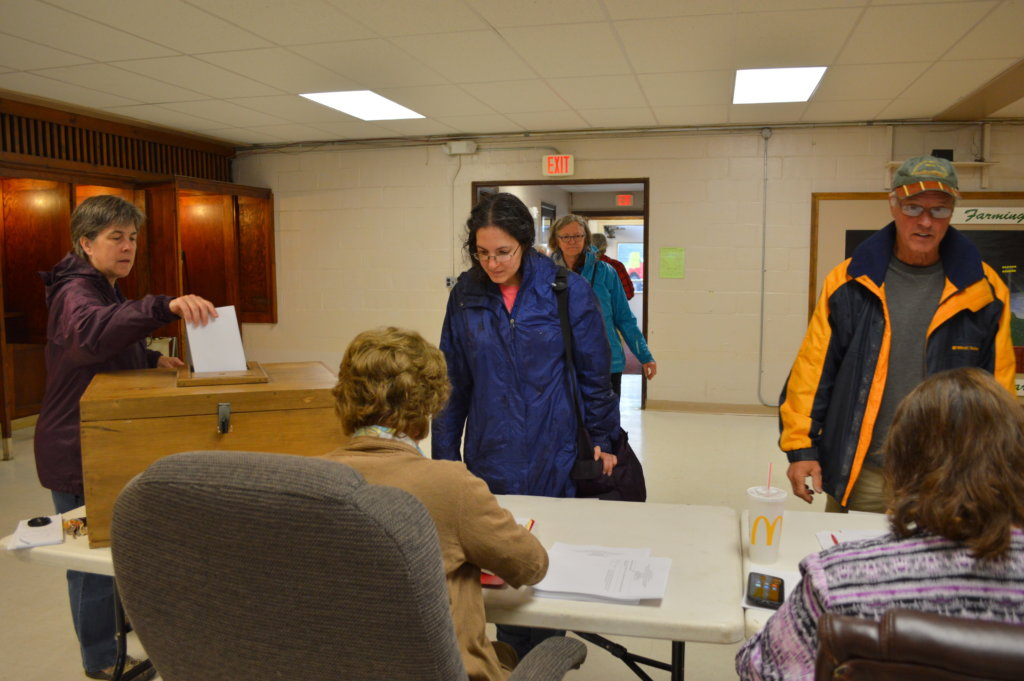 Crystal Woehrle-Logan, of Farmington, center, gets a ballot to vote on the Regional School Unit 9 budget Tuesday at the Community Center in Farmington.