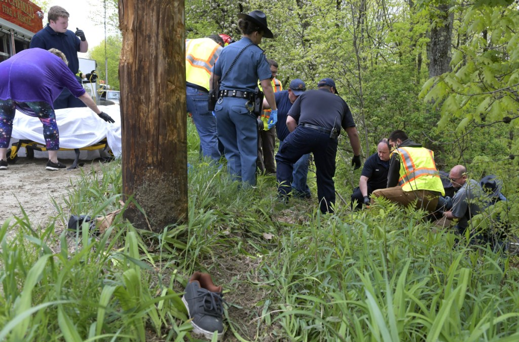 Firefighters and police carry the victim of a dirt bike accident Sunday morning on Oak Hill Road in Litchfield to an ambulance. Derek Parker, 35, died later of injuries he suffered in the morning accident, according to state police.