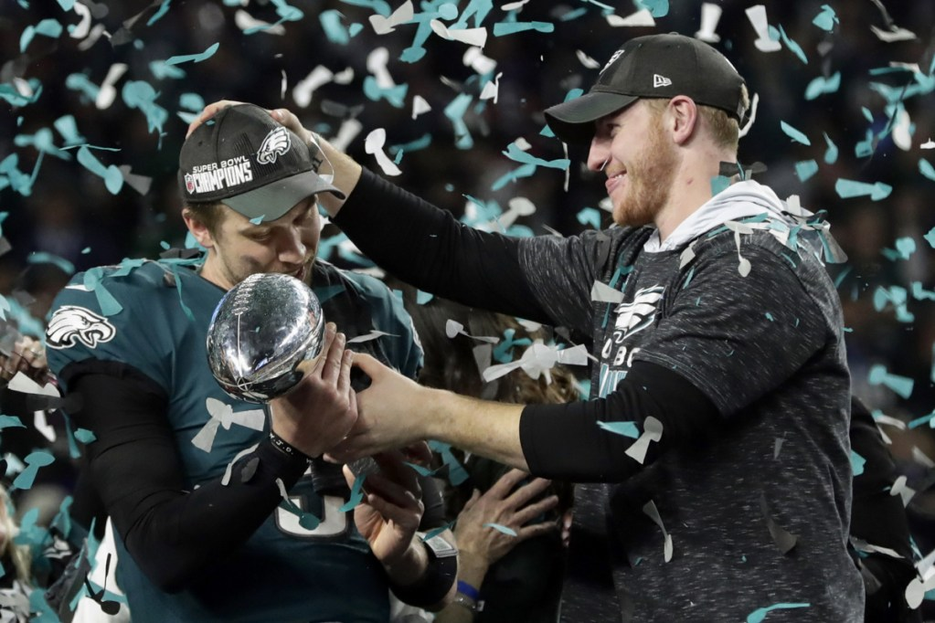 Philadelphia Eagles quarterback Carson Wentz, right, celebrates with Nick Foles after winning the Super Bowl in Minneapolis in February. President Trump has called off a visit by the Eagles to the White House, initially saying the team disagreed with him about the need to stand during the national anthem. It turns out that none of the Eagles champions had taken a knee during the anthem in 2017.