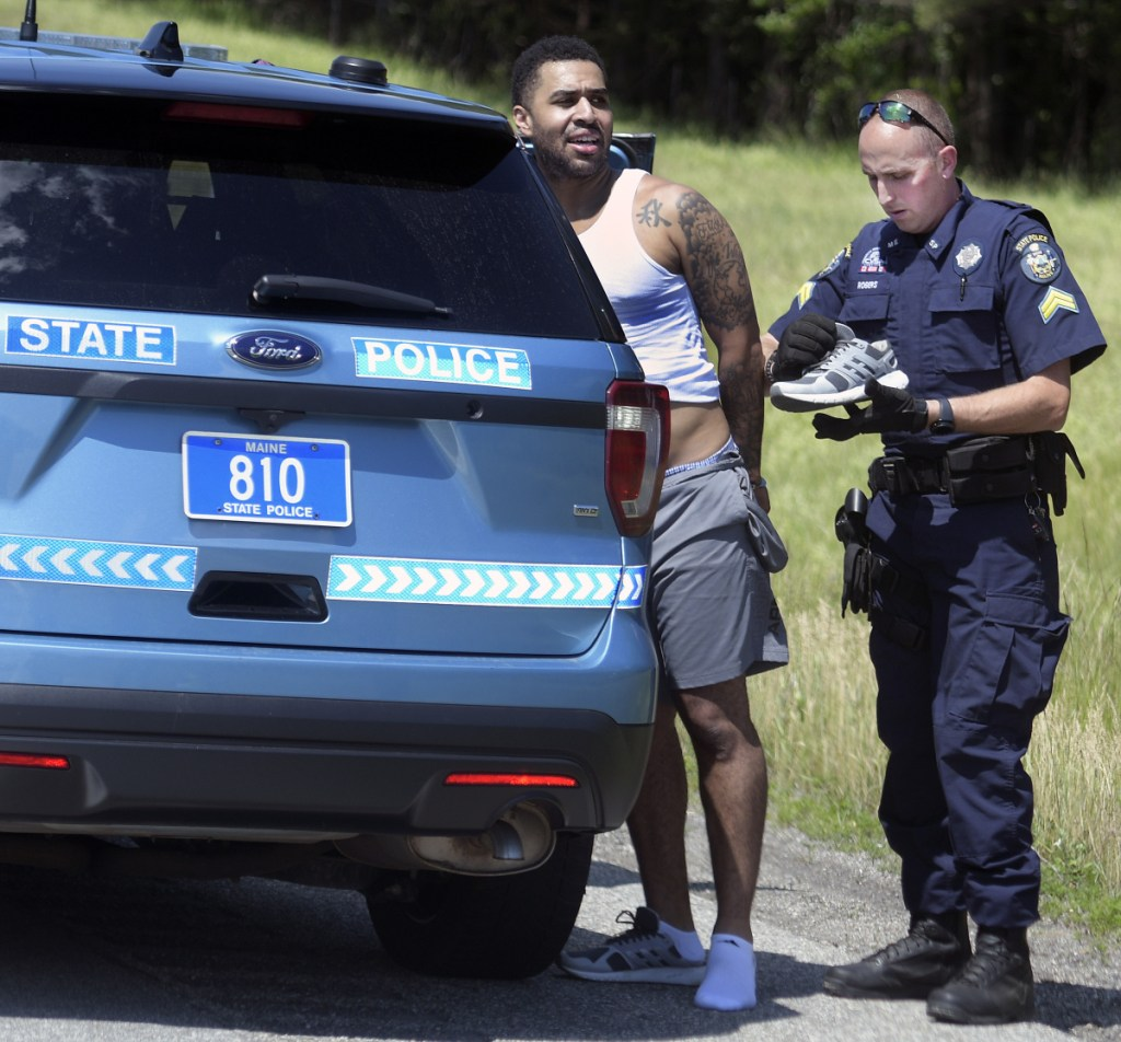 State police Cpl. Chris Rogers examines the clothes of Lenwood Williams, who was arrested Friday on the Maine Turnpike after a pursuit on the highway.