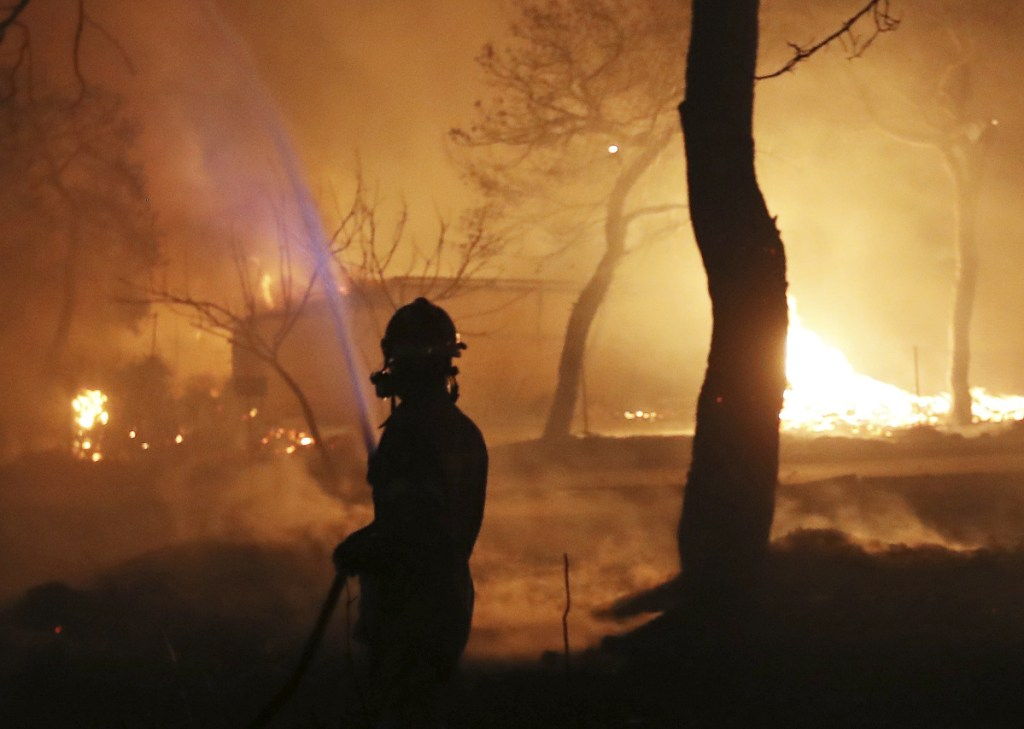 """Wildfires whipped up by gale-force winds sent tourists and residents fleeing Tuesday in Greece. """"I grabbed a beach town. It saved my life,"""" resident Andreaas Passios said."""