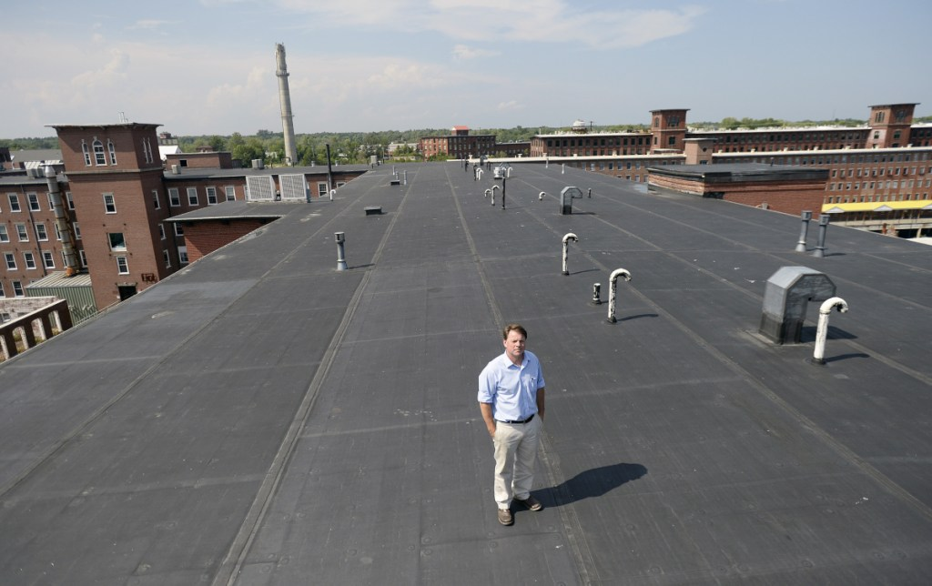 Scott Joslin, general manager of Pepperell Mill Campus in Biddeford, stands on the roof of one of his company's historic mill buildings. On Friday, his company announced plans to install nearly 1,200 rooftop solar panels to help power the campus.