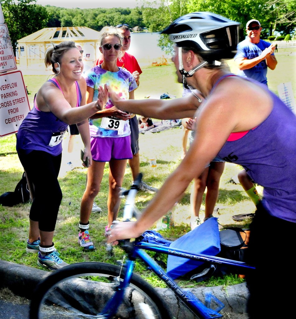 Runner Jess McKay, left, and cyclist Adrian Phair hand-off at the boat landing in Oakland as they compete in the OakFest triathalon in their respective sports on July 23, 2017.