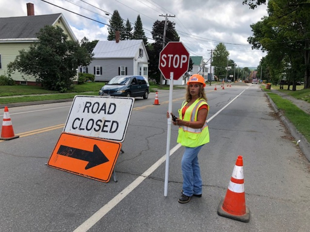 Susan Dorval, of Oakland, works Wednesday diverting traffic on North Avenue in Skowhegan during construction of a combined sewer overflow project, which fell behind schedule last year and is due to be completed in September.