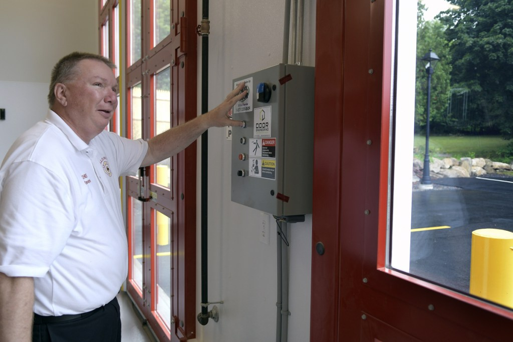 Hallowell Fire Chief James Owens opens the doors on the engine bays Tuesday at the Hallowell Fire Station. The doors, at a cost of $60,000 each, open horizontally to permit fire engines to exit and enter.