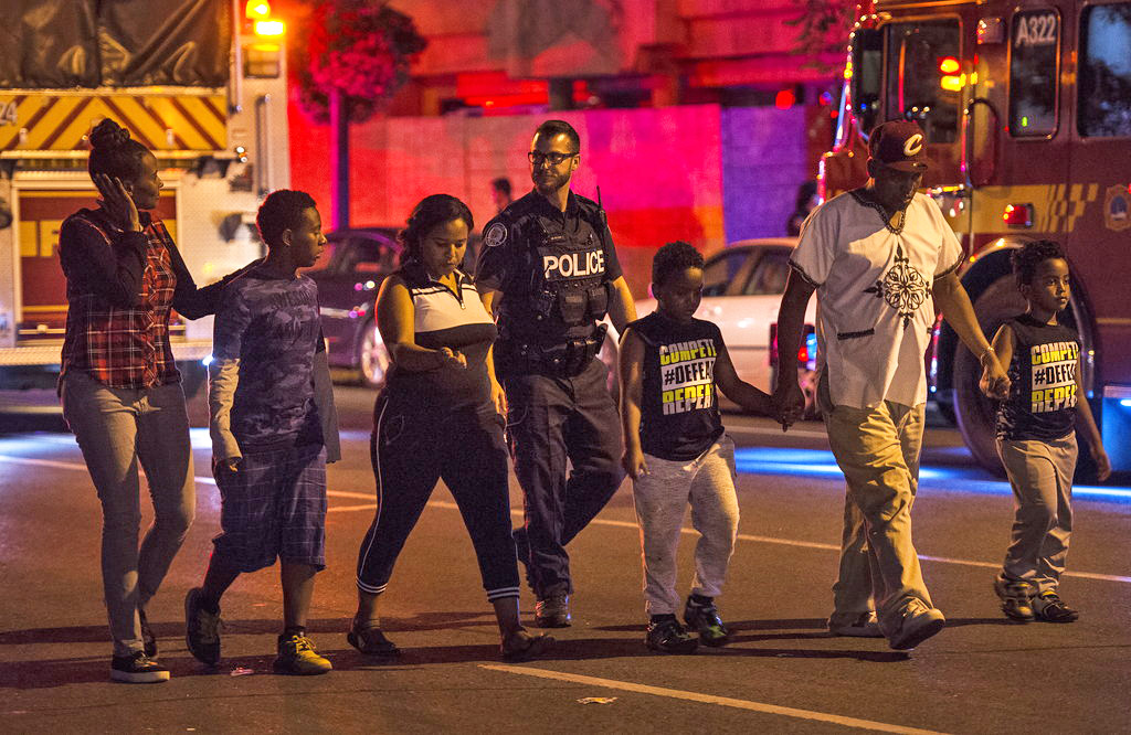 Police escort civilians away from the scene of a shooting Sunday night in Toronto.