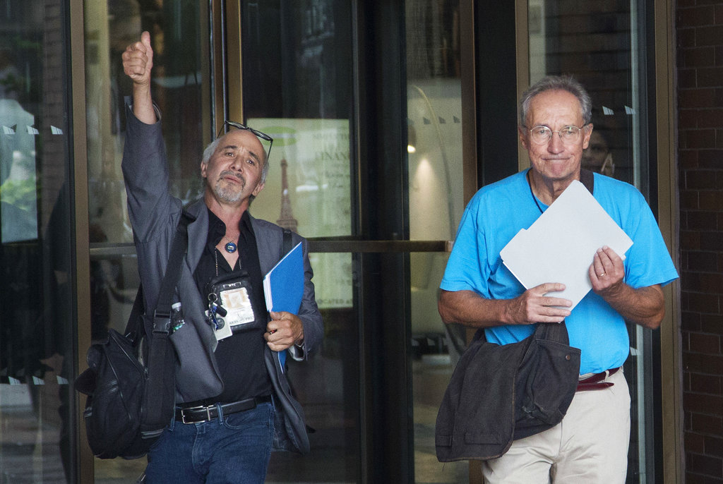 New York Daily News staff photographers Todd Maisel, left, and Andrew Savulich walk out of the newspaper's office after being laid off, Monday.