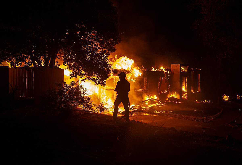 A firefighter works to battle the Carr Fire at a home in Redding, Calif. on Thursday, July 26, 2018.