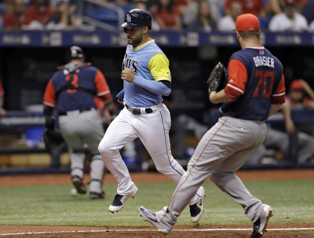 Tampa Bay's Kevin Kiermaier scores on a wild pitch by Boston Red Sox relief pitcher Ryan Brasier, right, as catcher Sandy Leon chases the ball during the Rays' 5-1 victory over Boston on Saturday evening in St. Petersburg, Florida.