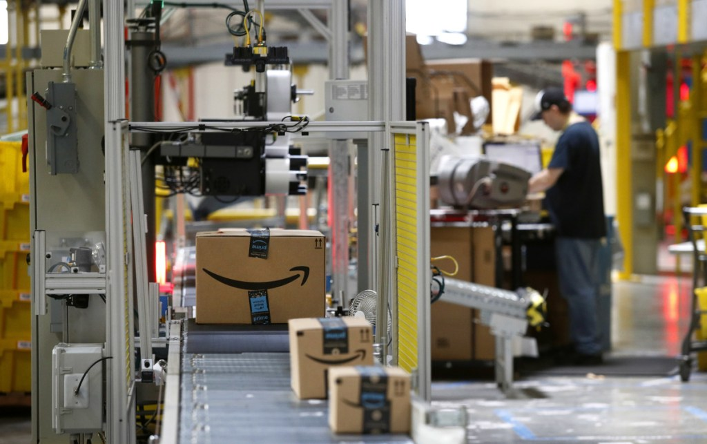 """A machine scans packages at an Amazon fulfillment center in Baltimore. Amazon is paying workers to defend the company on Twitter, reassuring critics that they make a living wage and are allowed to take bathroom breaks. One worker tweeted: """"We are totally happy working for an amazing company."""""""