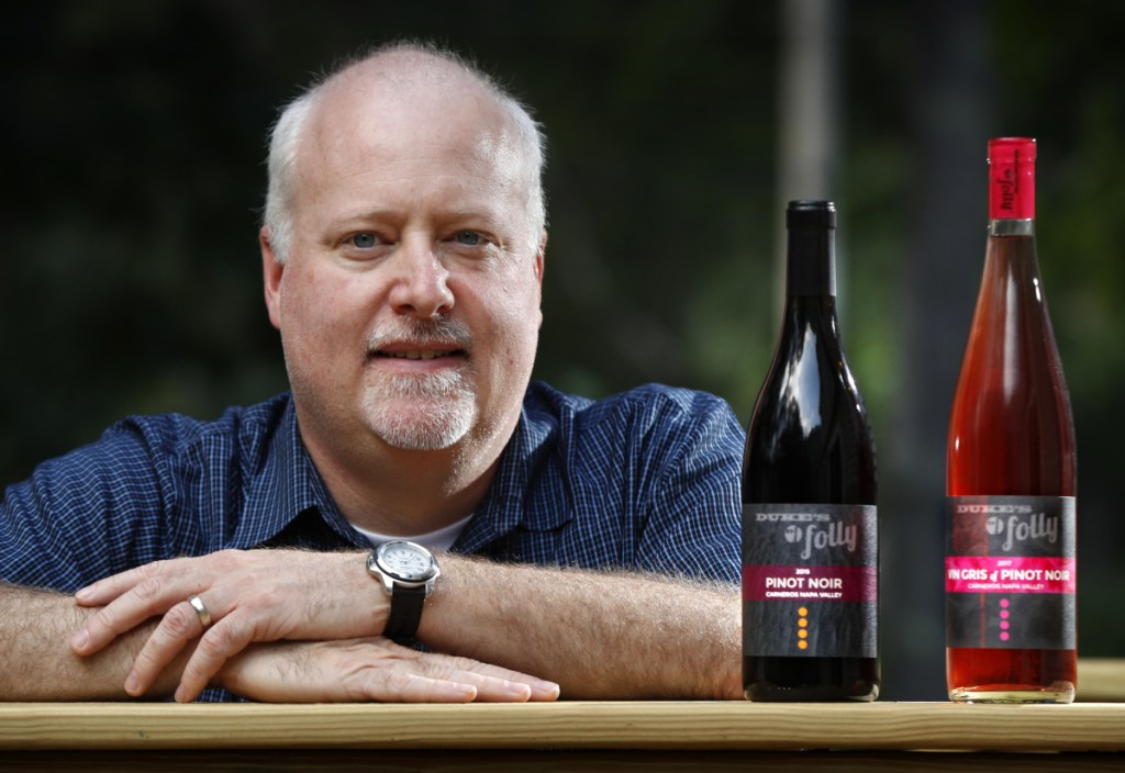 """Kirk Duke, whose family runs a California winery, shows some bottles of wine at his home in Falmouth. Duke University had blocked the company from registering the trademark Duke's Folly, saying it """"deceptively"""" implied a tie to the North Carolina university. The family's response? That's """"absurd."""""""