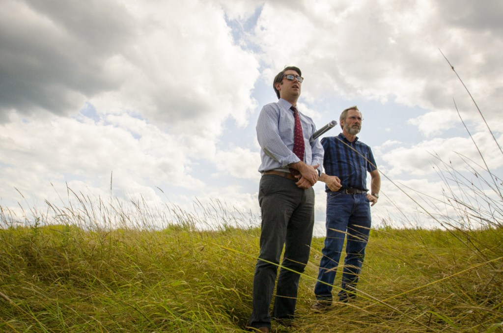 Garvan Donegan, Central Maine Growth Council senior economic development specialist, left, and Greg Brown, Waterville city engineer, survey the landfill off Webb Road in Waterville in August 2017. Plans are are moving forward in the development of a 20-megawatt solar farm on the site that could power 3,750 homes.