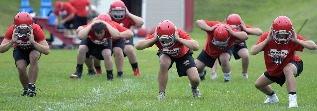 Cony High School football players work through some drills during practice Monday morning in Augusta. Monday marked the first day fall sports teams could start practicing.