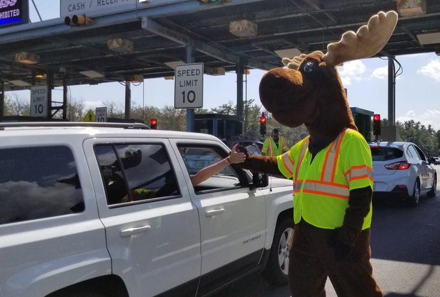 The Maine Turnpike Authority's Miles the Moose high-fives motorists as they leave Maine on Labor Day at the York Toll Plaza. Traffic was heavy but steady throughout the day on the Maine Turnpike.