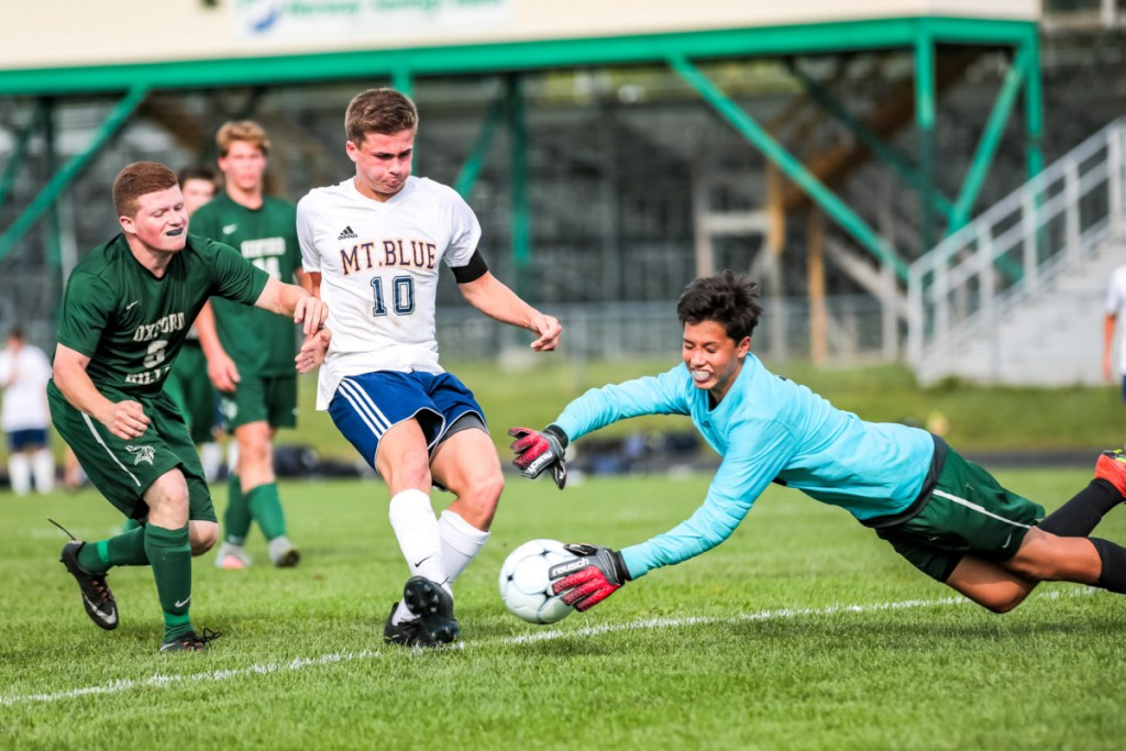 Oxford Hills goalkeeper Sam Morton comes out of the net to deny Mt. Blue's Sam Smith in first-half action at Gouin Athletic Complex in Paris on Tuesday.