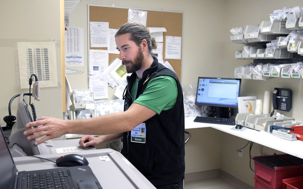 MaineGeneral Medical Center nurse Ethan Perry checks medication Wednesday at the Augusta hospital. The registered nurse said he's started working a part-time job to reduce the debt from obtaining his nursing degree.