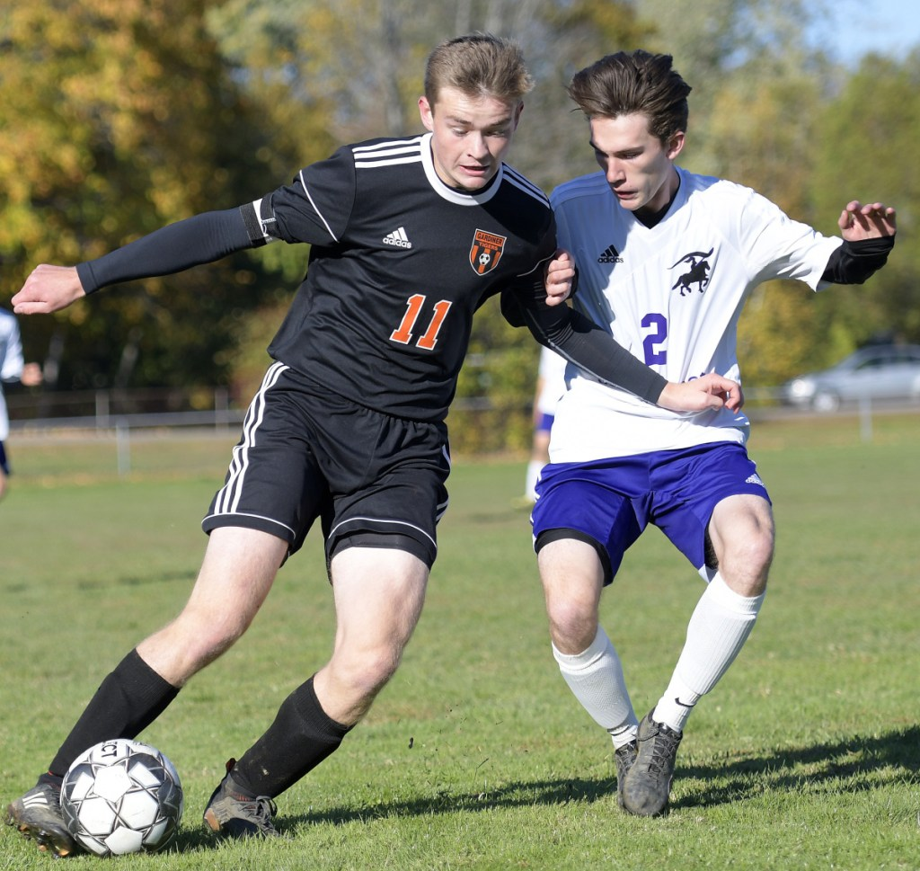 Gardiner's Casey Bourque, left, fights for position with John Bapst's Connor Reese during a Class B North prelim game Friday  in Gardiner.