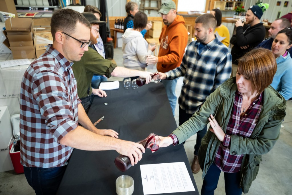Nathan Hall, left, co-owner of Kennebec Cider Company in Winthrop pours a sample for Briana Dyer, of Sebec, on Saturday afternoon in Winthrop. The tasting event was part of the third annual Ciderfest held at the location.