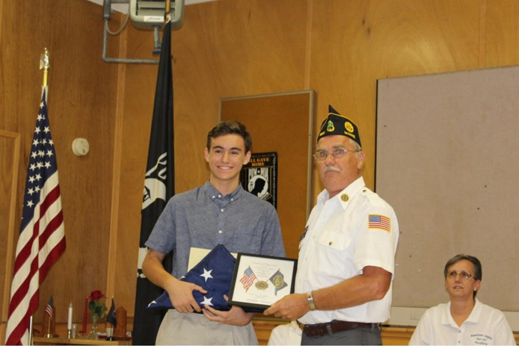 Hagen (Joki) Wallace, left, present an American flag to Commander in Chief is Clayton York during an American Legion and Auxiliary Post 163 special meeting.