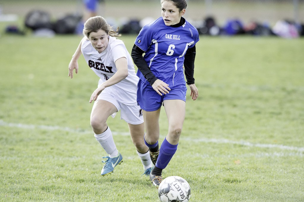 Oak Hill's Gabby Chessie, right, dribbles the ball by Greely's Kerry Roberts during a Class B South quarterfinal game in Wales.