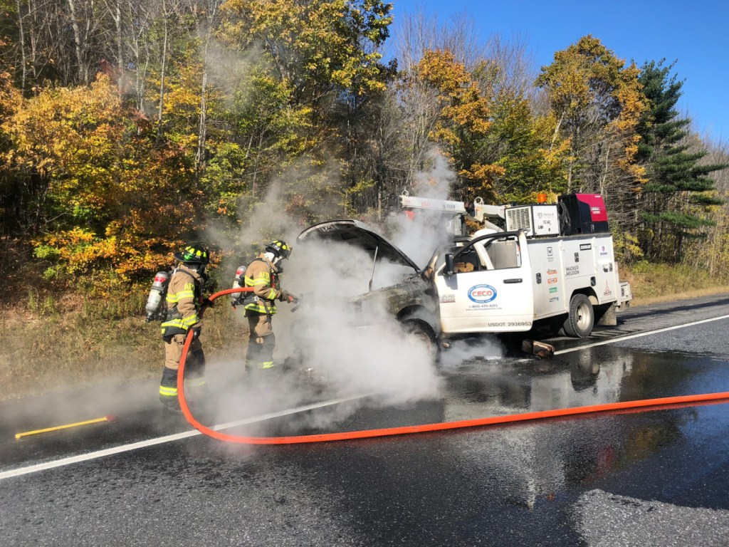 Augusta firefighters extinguish a fire in a heavy equipment service truck Friday on Interstate 95 in Augusta. The fire caused the southbound lanes to be closed briefly in late morning, backing up traffic for at least 3 miles.