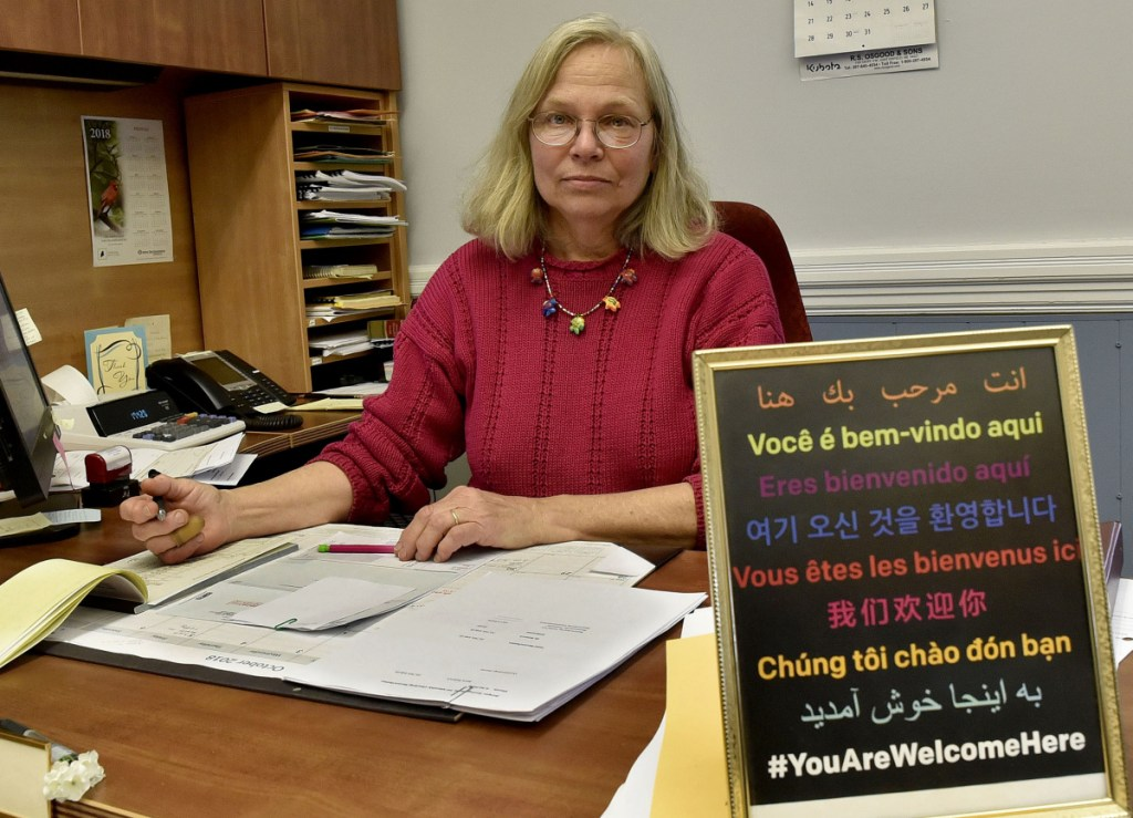 """Franklin County Treasurer Pamela Prodon, at her desk at the Franklin County Courthouse in Farmington on Monday, displays a sign on her desk that states """"You Are Welcome Here"""" in nine languages similar to the signs displayed by residents, including her in-laws, near the Tree of Life synagogue in Pittsburgh where a gunman killed 11 worshipers on Saturday."""