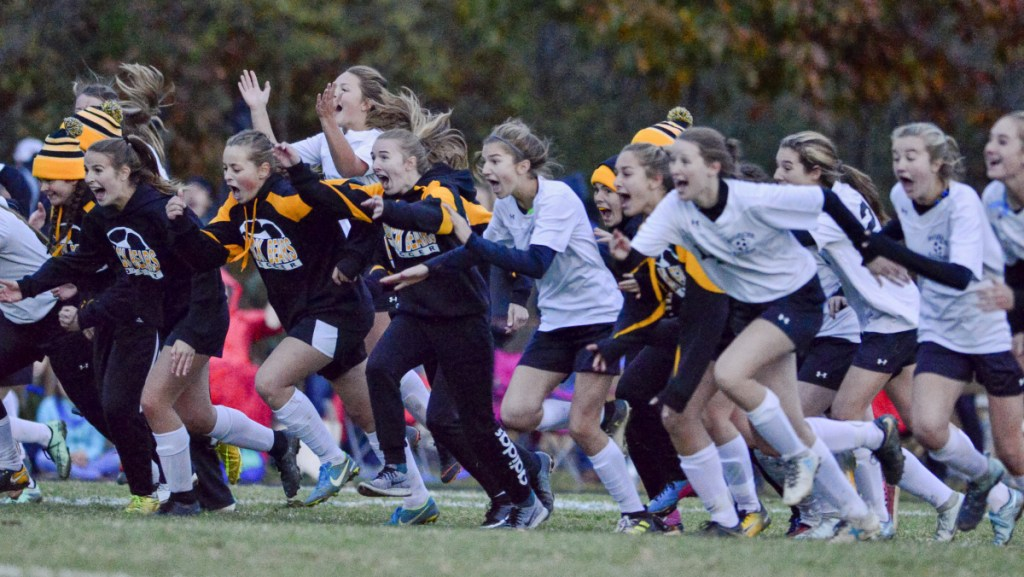 The Maranacook girls soccer team runs onto the field to celebrate after beating Traip Academy in the Class C South regional final Wednesday in Kittery.