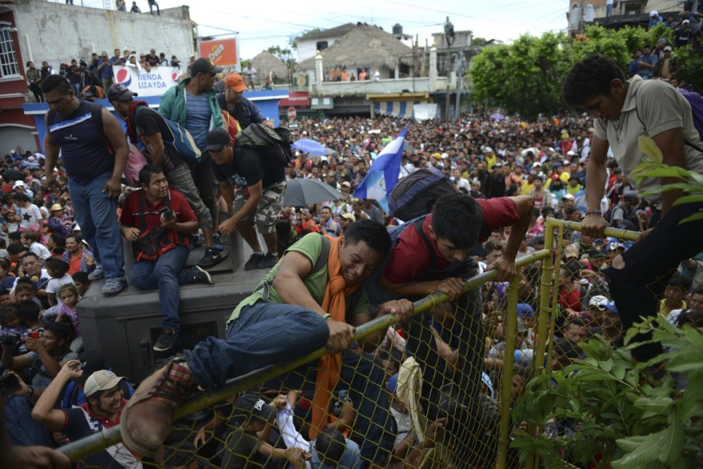 Thousands of Honduran migrants rush across the border toward Mexico, in Tecun Uman, Guatemala, on Friday.