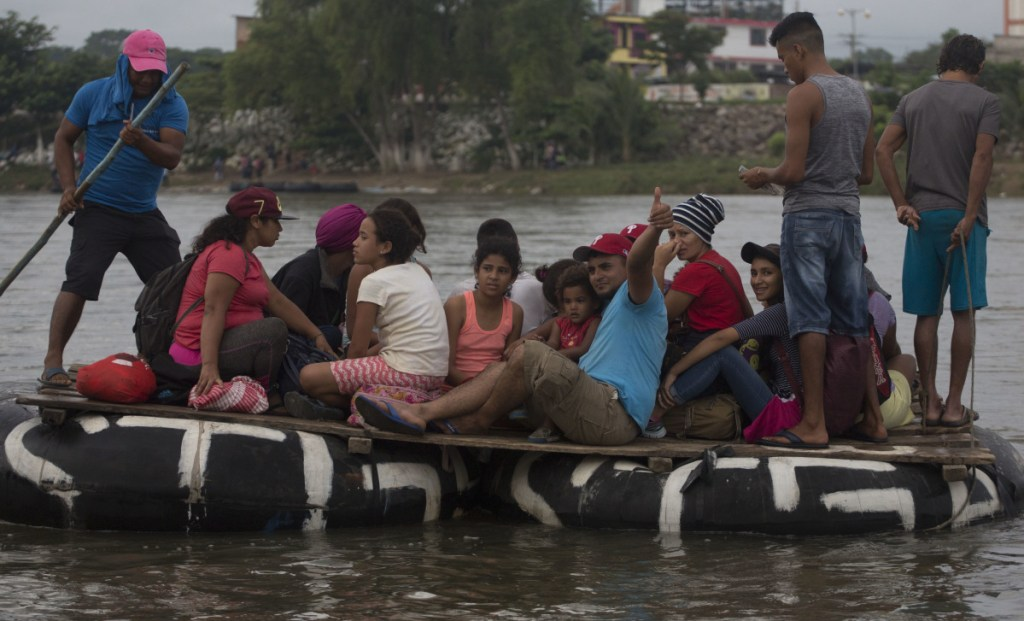 Honduran migrants cross the Suchiate River aboard a raft made out of tractor inner tubes and wooden planks, in Tecun Uman, Guatemala, on Saturday.