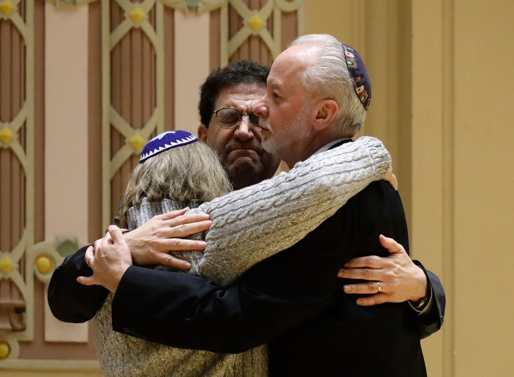 Rabbi Jeffrey Myers, right, of Tree of Life/Or L'Simcha Congregation hugs Rabbi Cheryl Klein, left, of Dor Hadash Congregation and Rabbi Jonathan Perlman during a community gathering held Sunday in the aftermath of the deadly shooting.