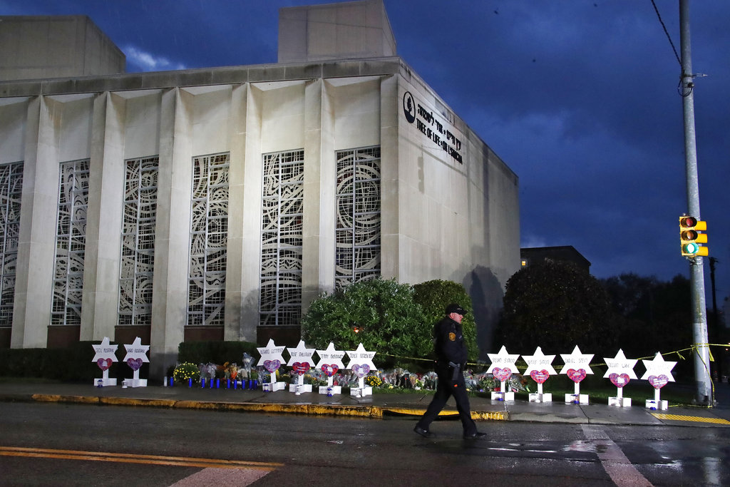 A Pittsburgh Police officer walks past the Tree of Life Synagogue and a memorial of flowers and stars in Pittsburgh on Sunday, in remembrance of those killed and injured when a shooter opened fire during services Saturday at the synagogue.
